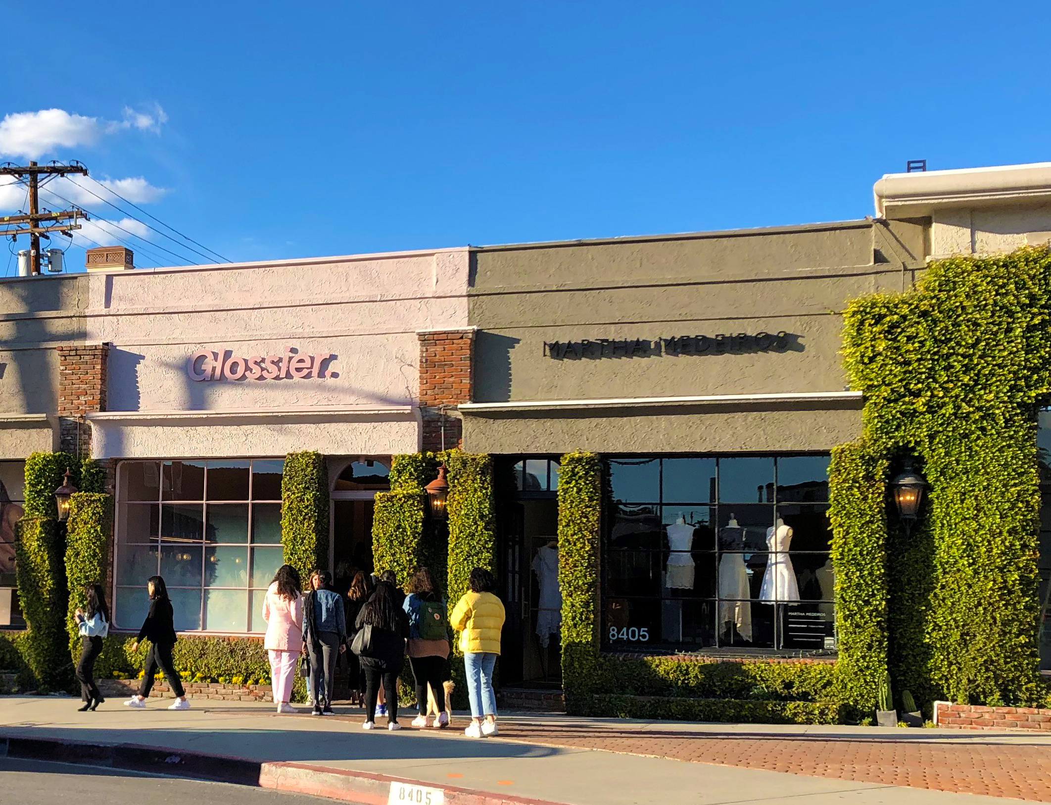 Shoppers wait in line to enter Glossier in California.