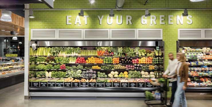 people walking in grocery store aisle