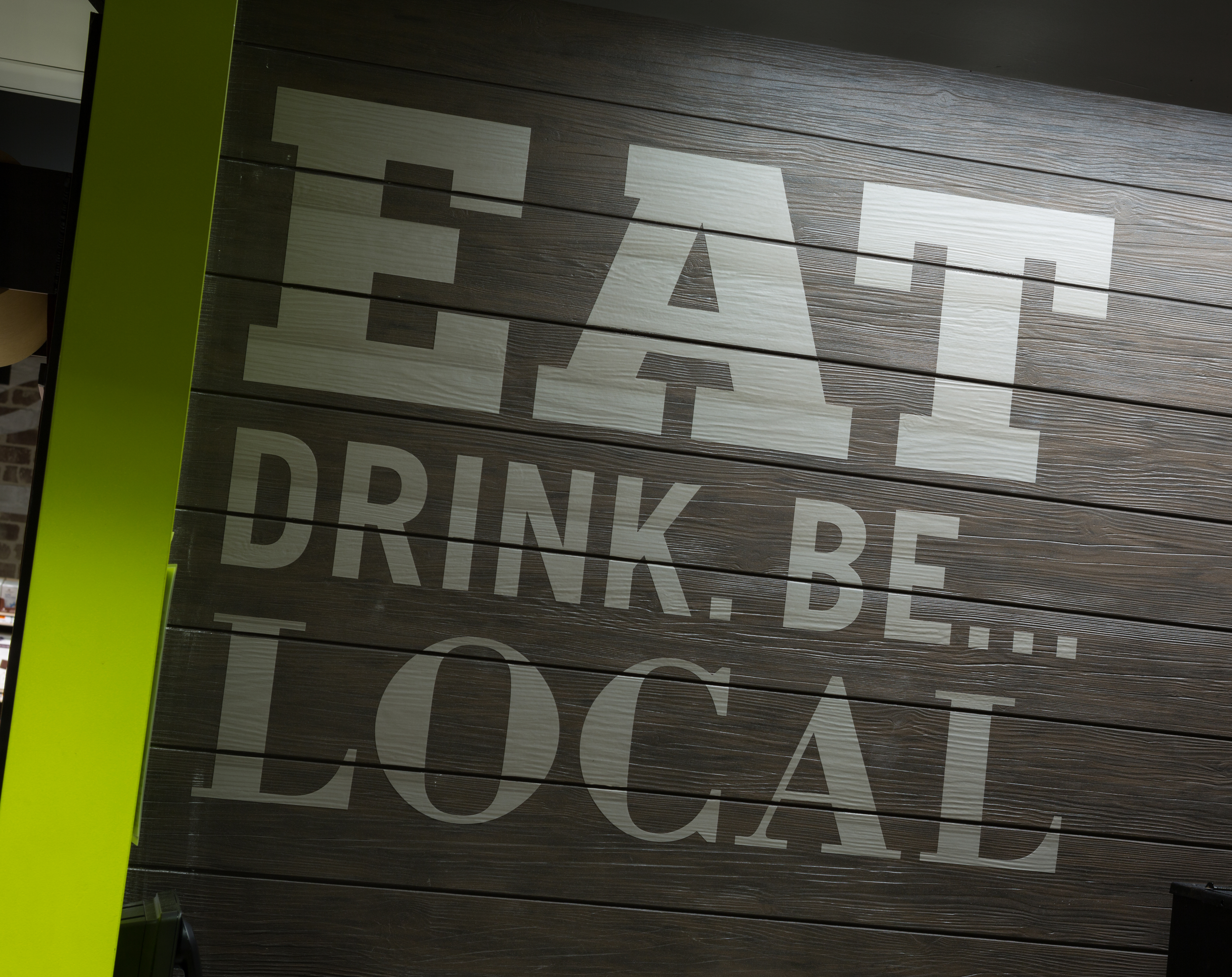 """""""Eat Drink. Be... Local"""" experiential graphics on a wood panel wall in Brothers Marketplace Medfield, MA"""