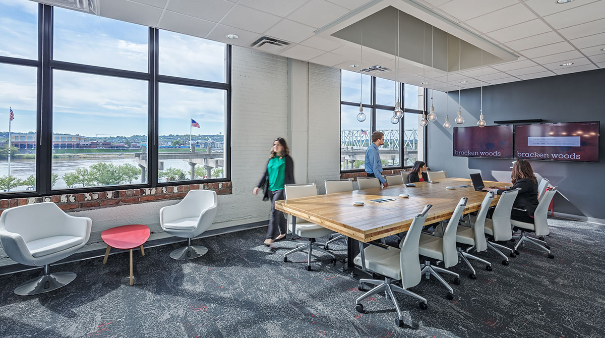 Employees gather around a conference table