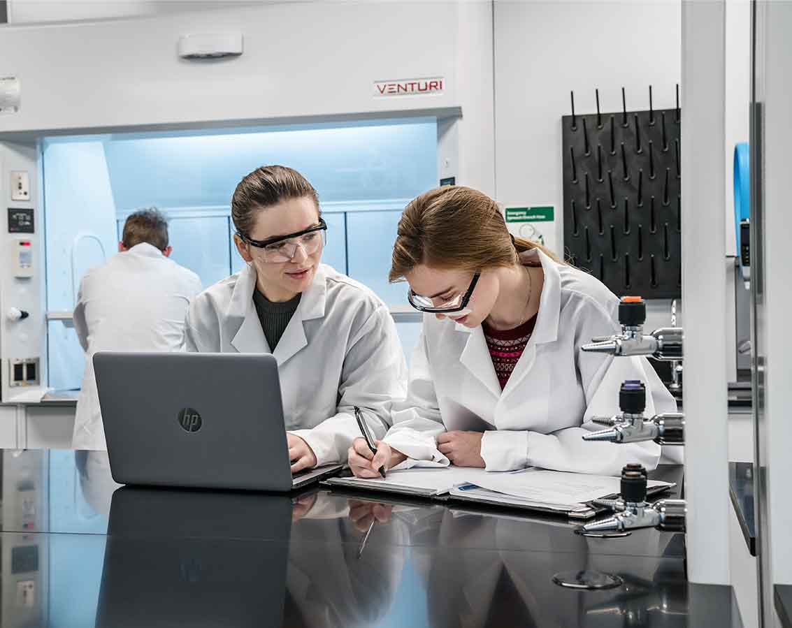 Two students share a computer while in a lab setting