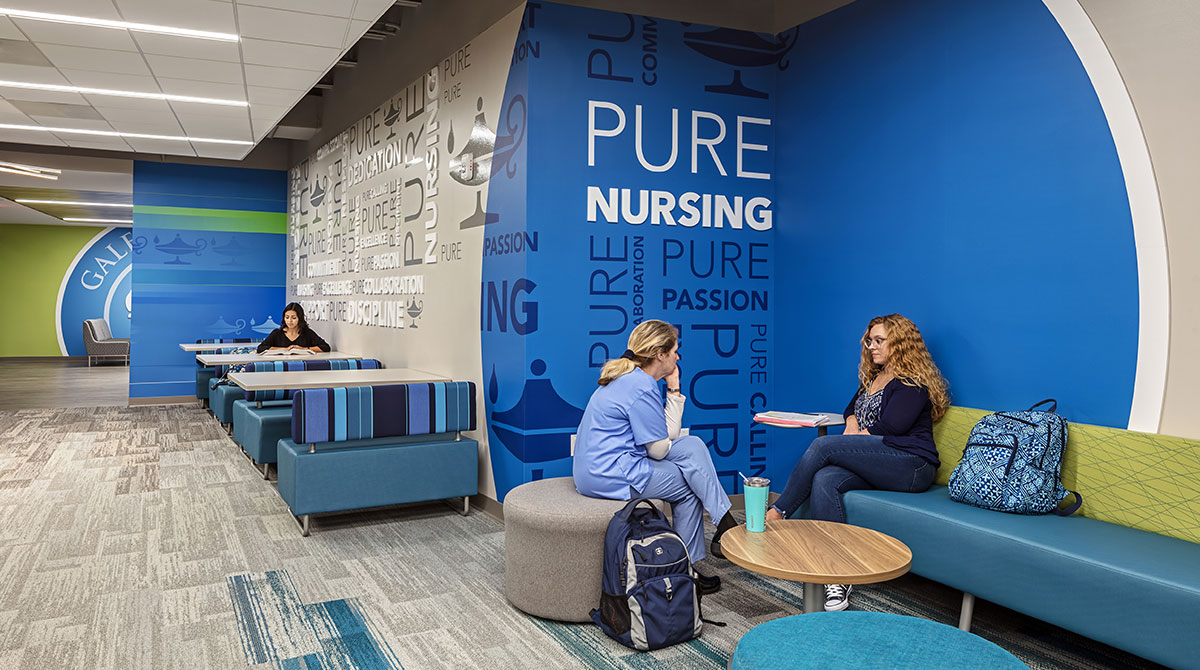 """Informal collaboration spaces with a """"Pure Nursing"""" graphic on the wall"""