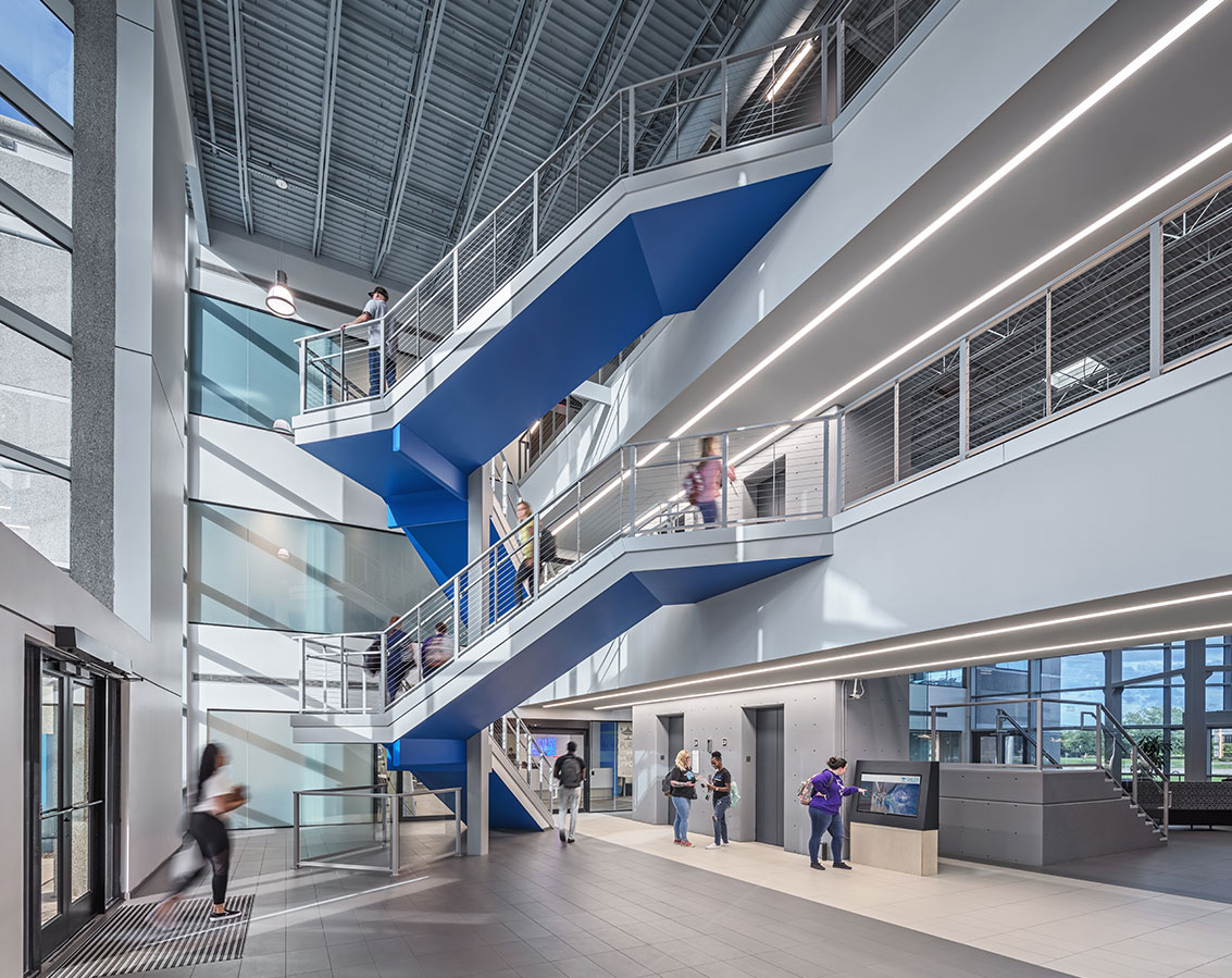 A staircase with blue accents connects multiple floors