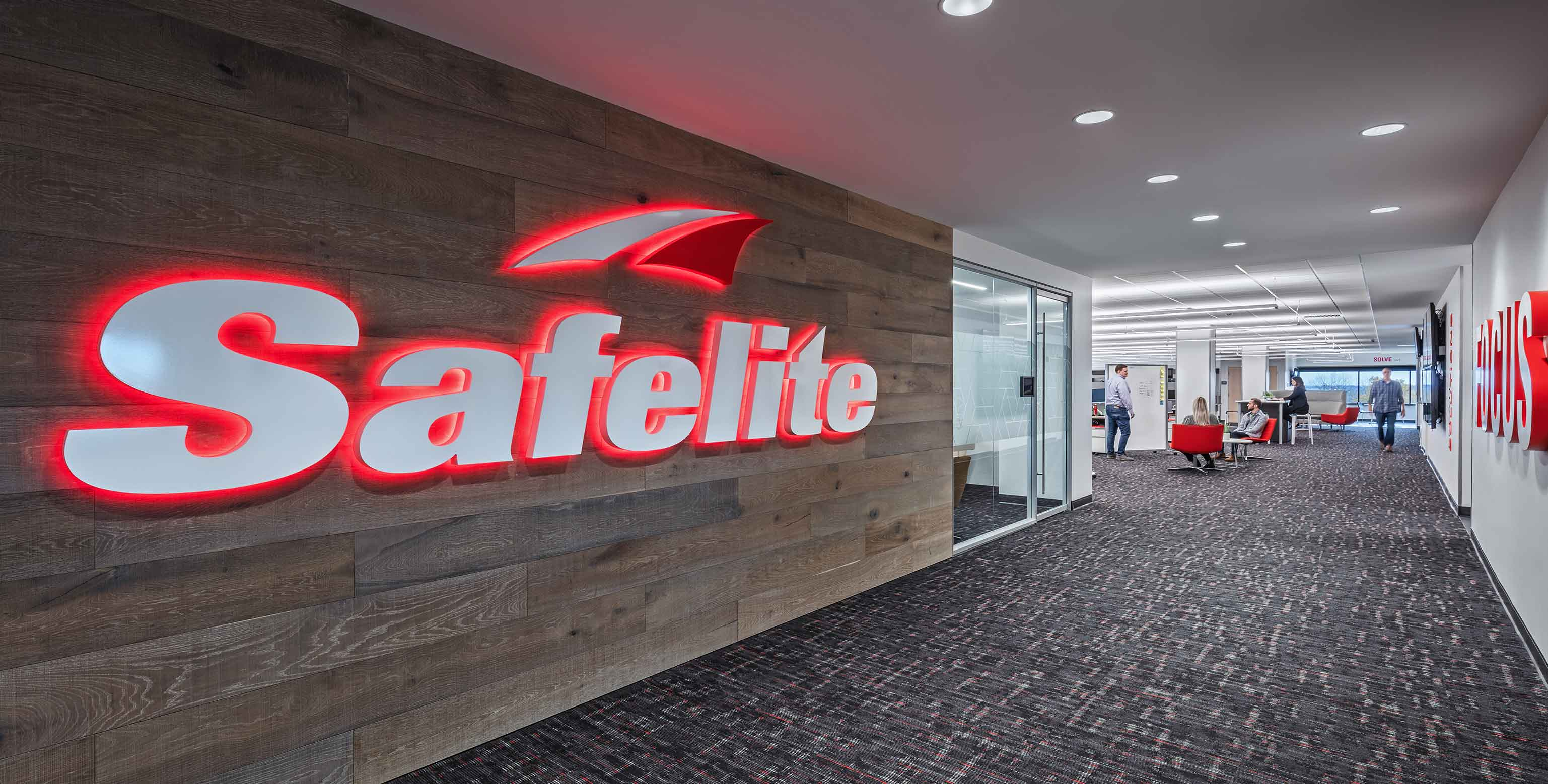 Safelite's logo shines bright on a wood panel wall