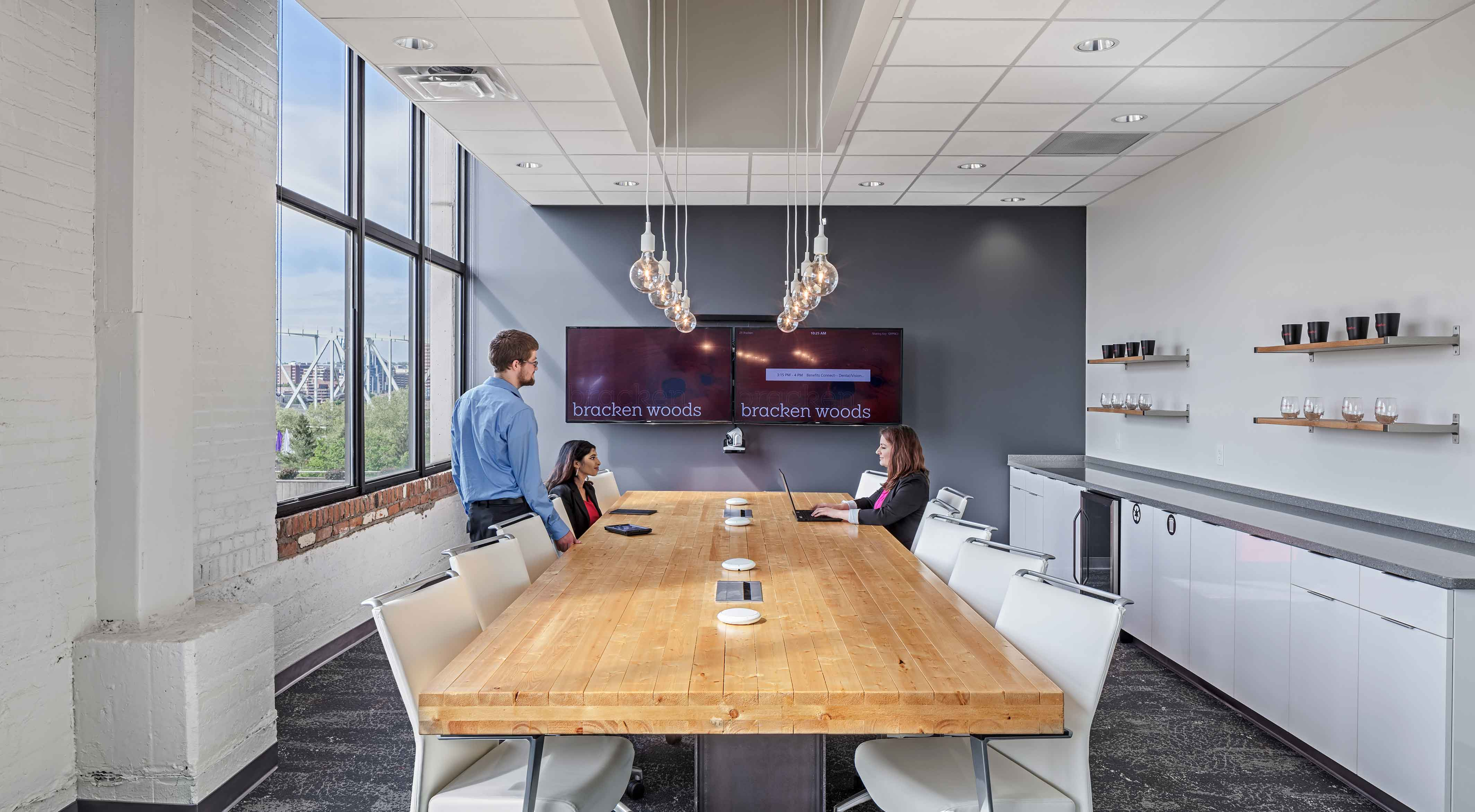 Employees gather in a conference room around a handmade table
