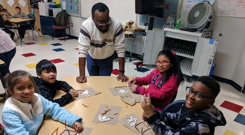 Four children sit as an adult man leads them through an activity