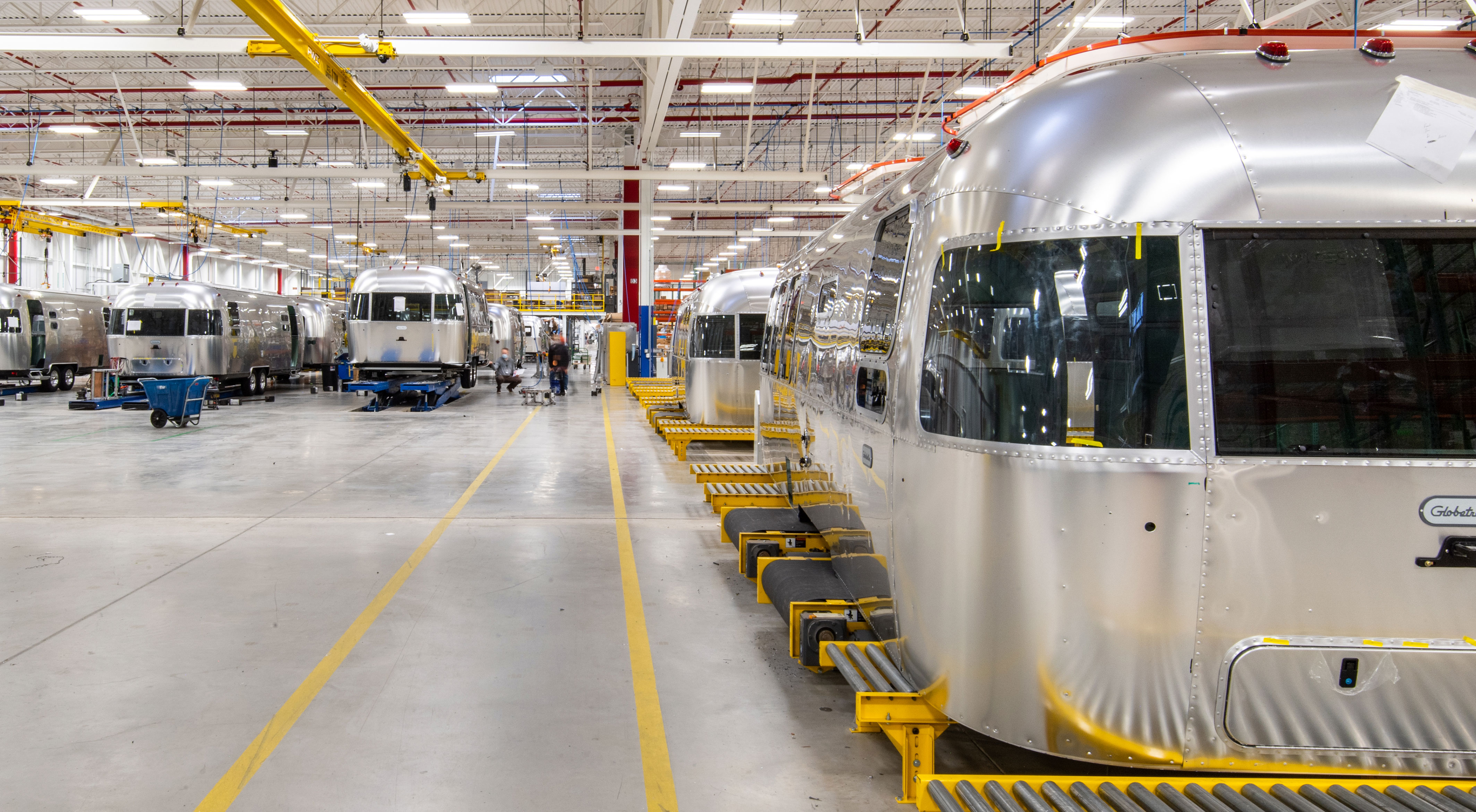 Multiple Airstreams are shown being worked on by employees