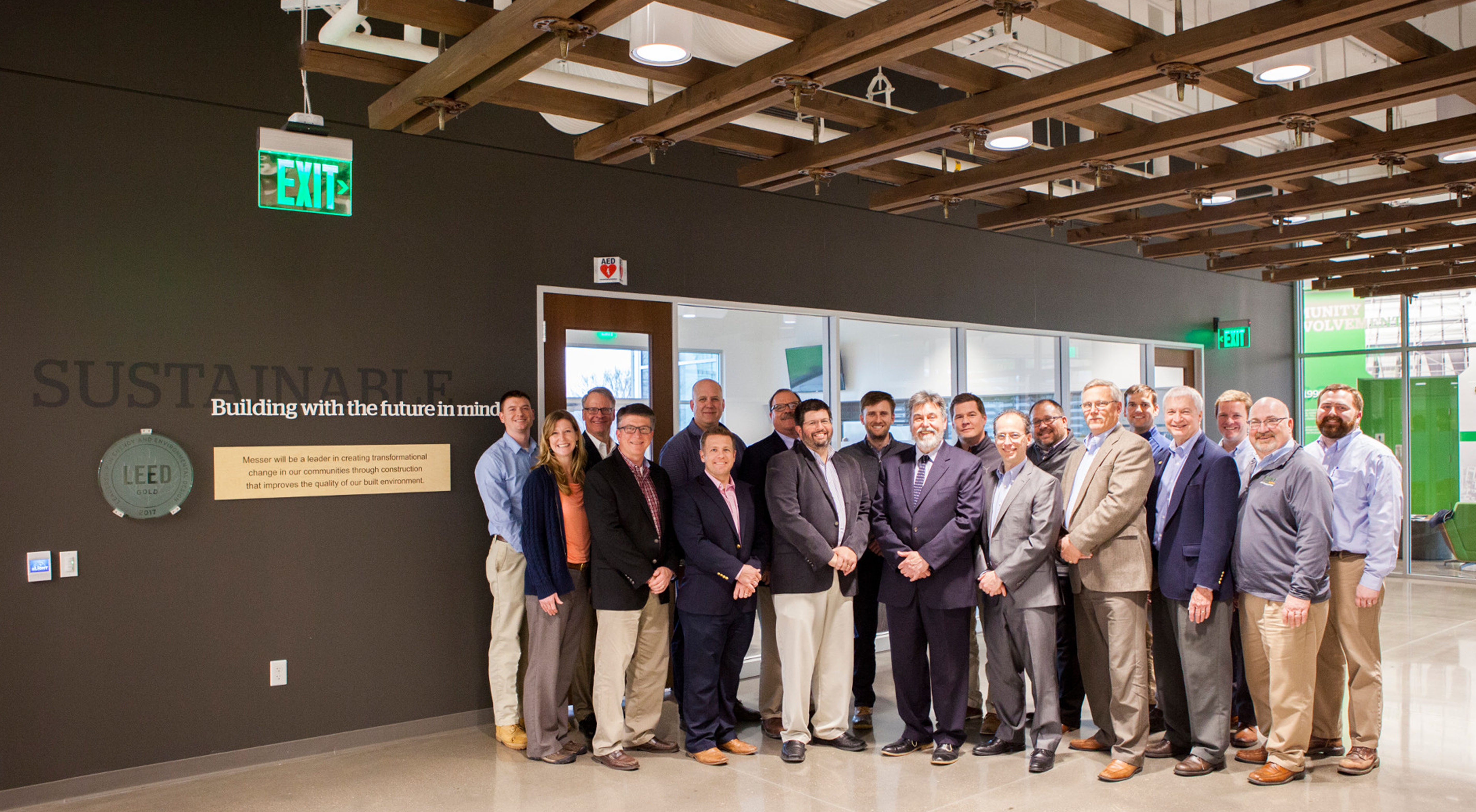 The project team stands beside signage talking about sustainability