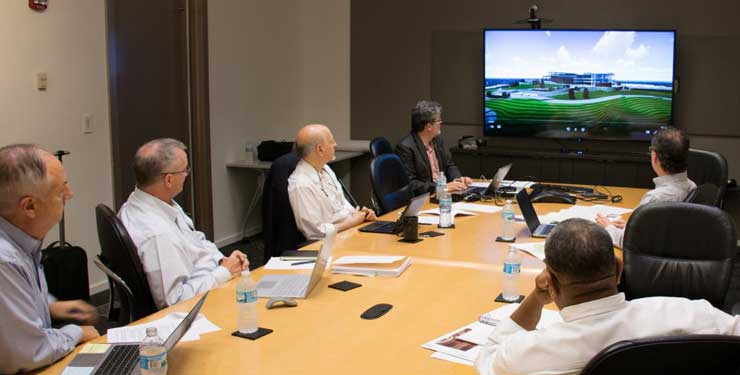 Group of people in conference room looking at tv