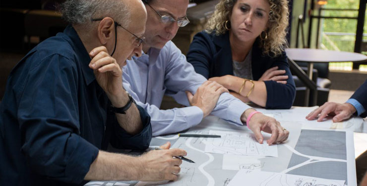 three people looking at a building plan