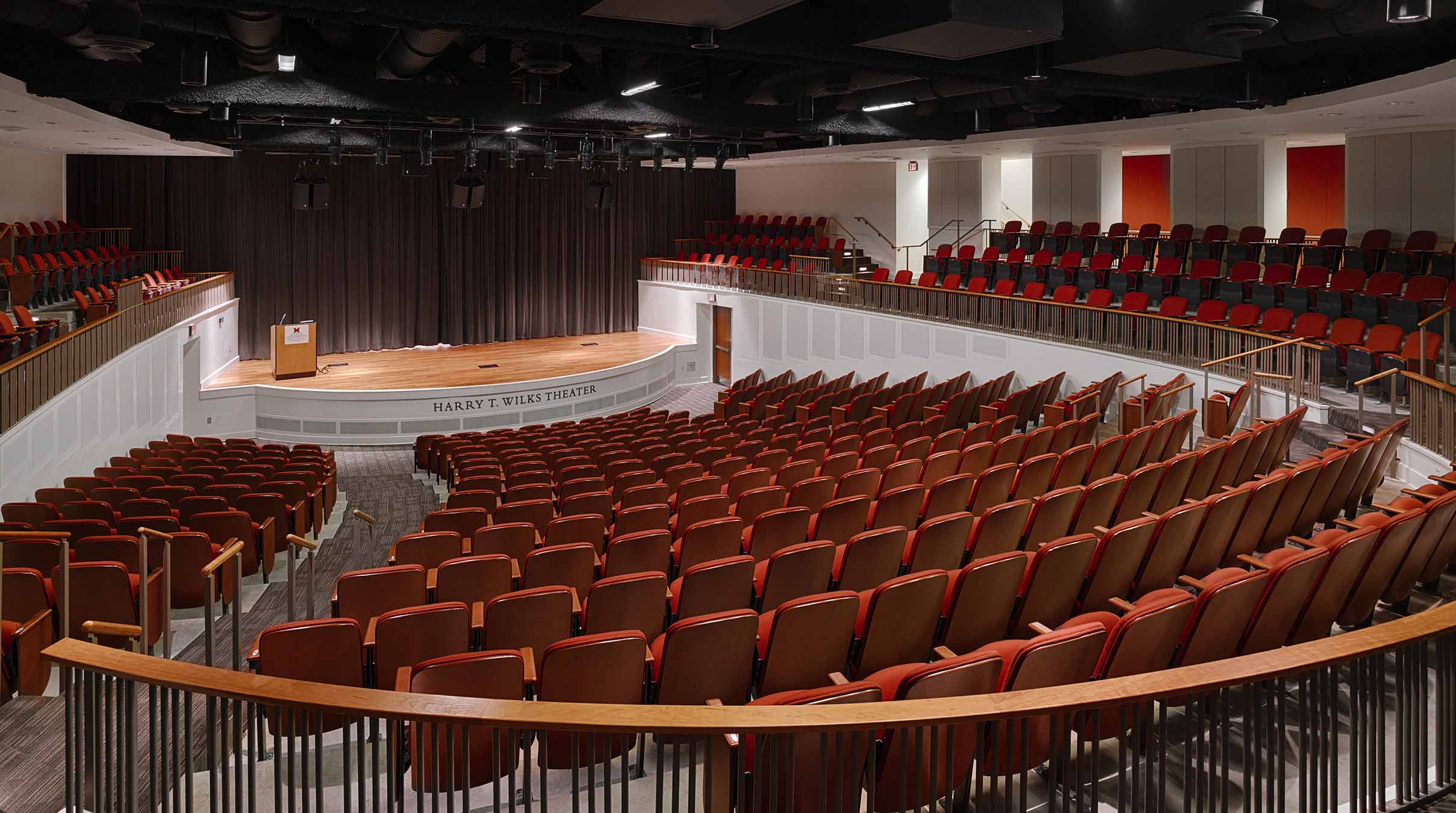 500-seat theater with red seats and a natural wood stage