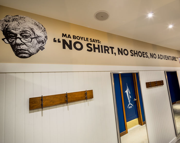"""Columbia fitting rooms with a wall graphic that reads, """"Ma Boyle says: 'No shirt, no shoes, no adventure.'"""""""