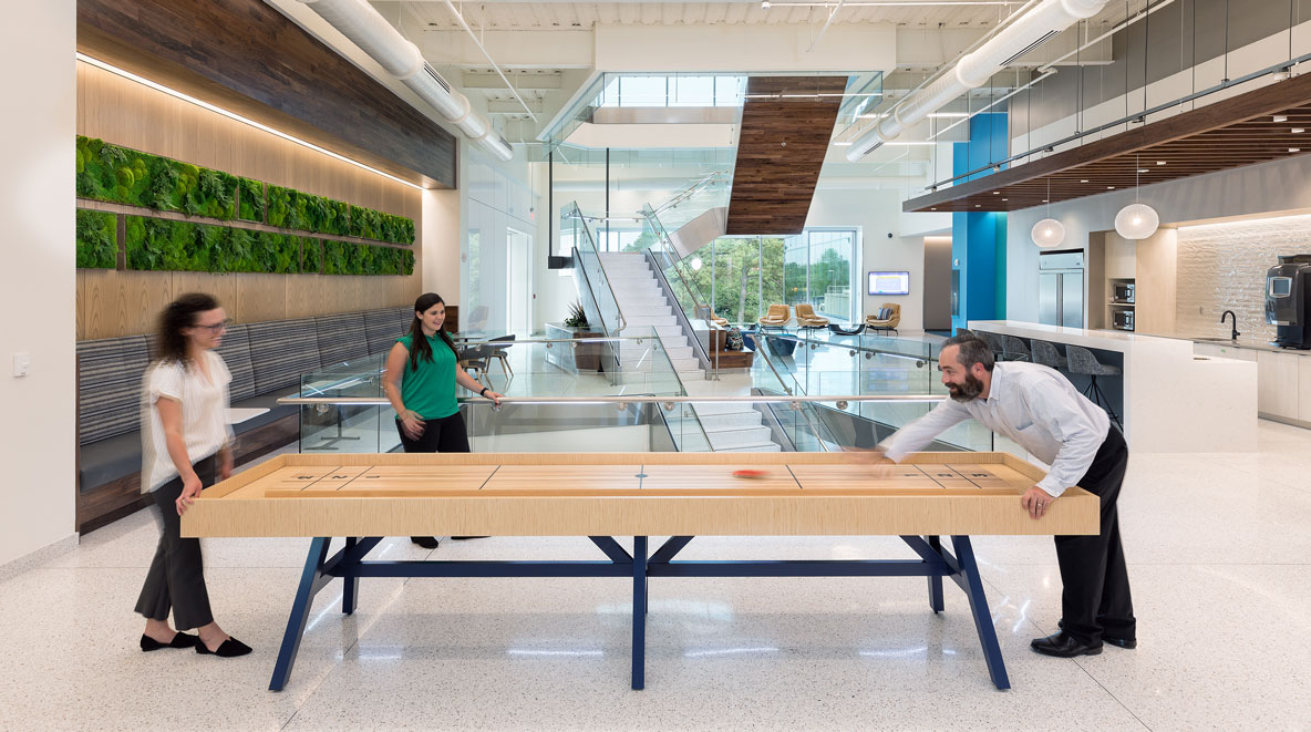 Three people playing table top shuffle board at Altria HQ