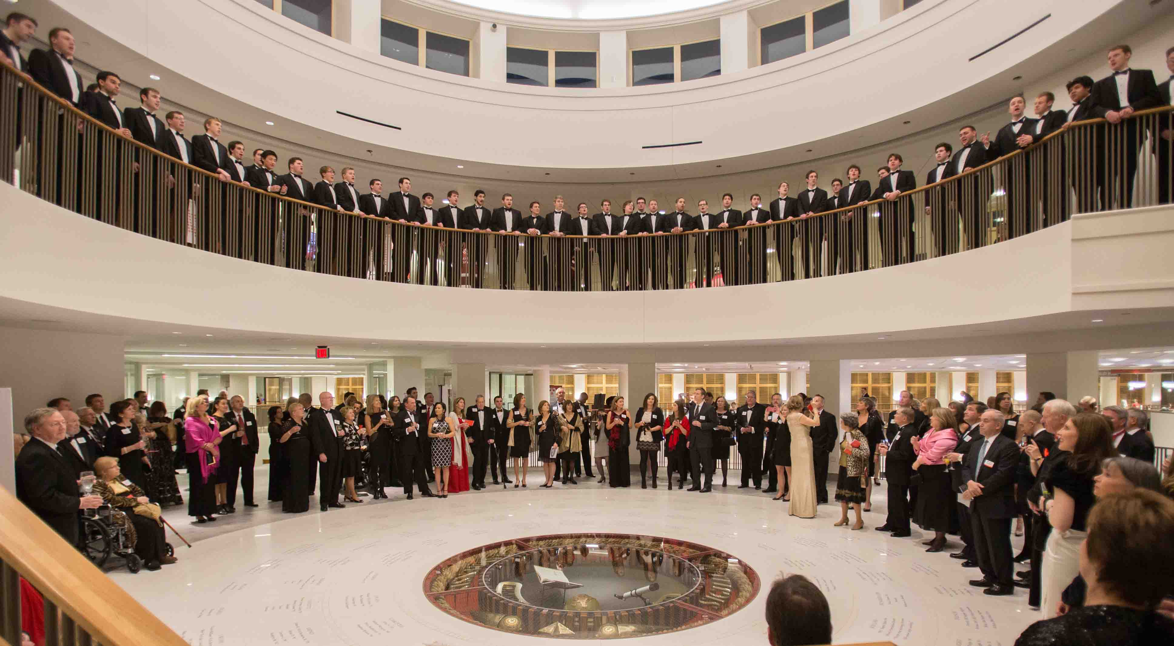 A glee club sings from the second floor of the Armstrong Student Center rotunda to a crowd below