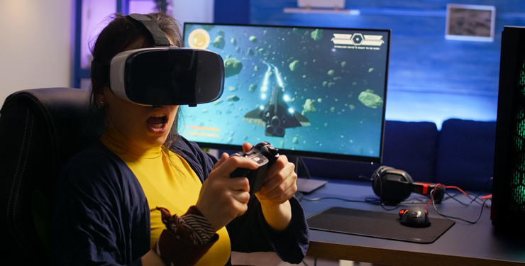 A woman wears a VR headset and sits at a computer