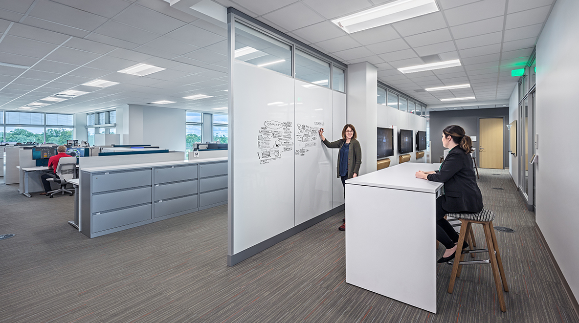 A collaboration zone—equipped with white boards and monitors—is near employee workstations.