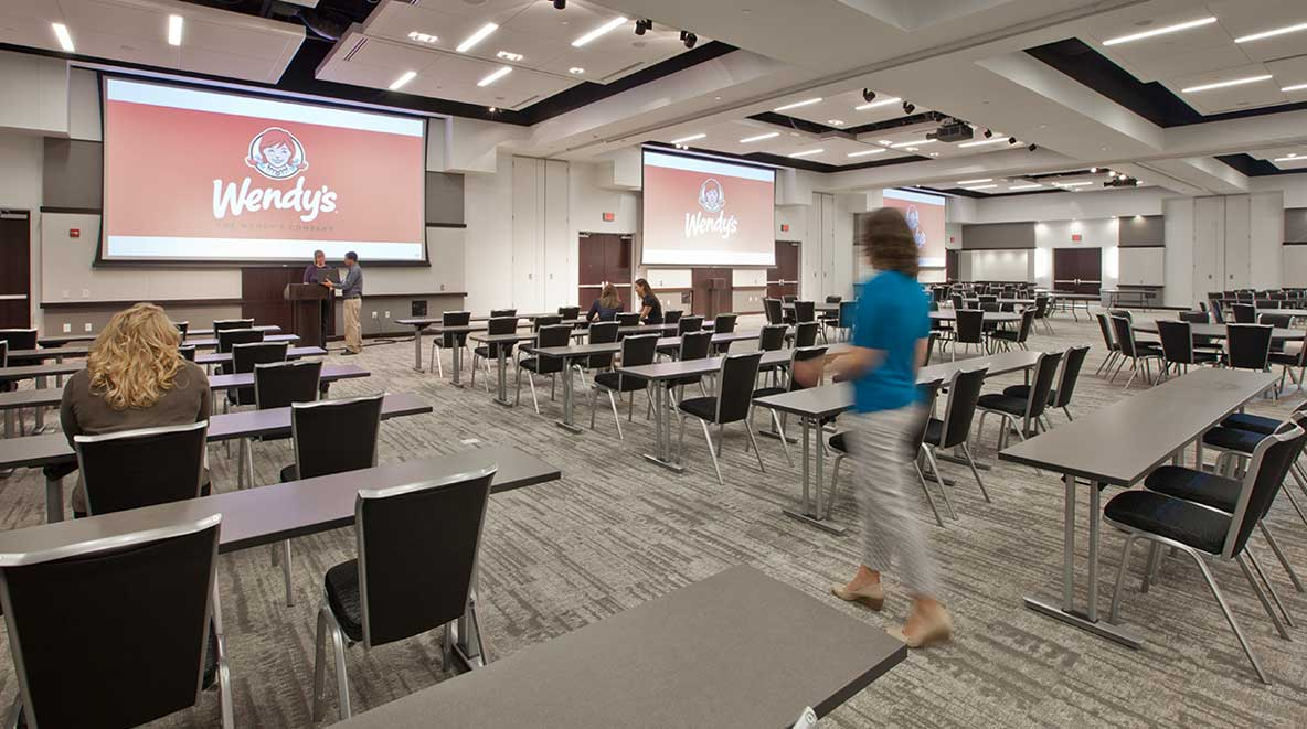 A modern conference room with two large projector screens.