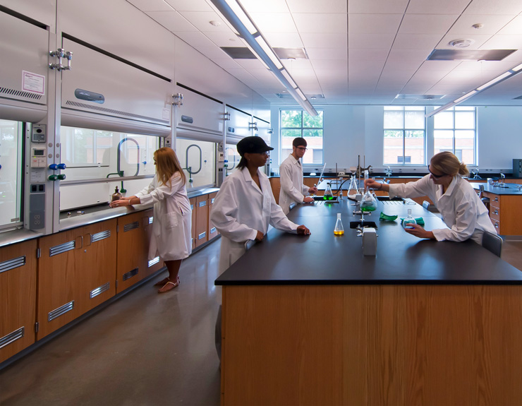 Students hover over a central lab table