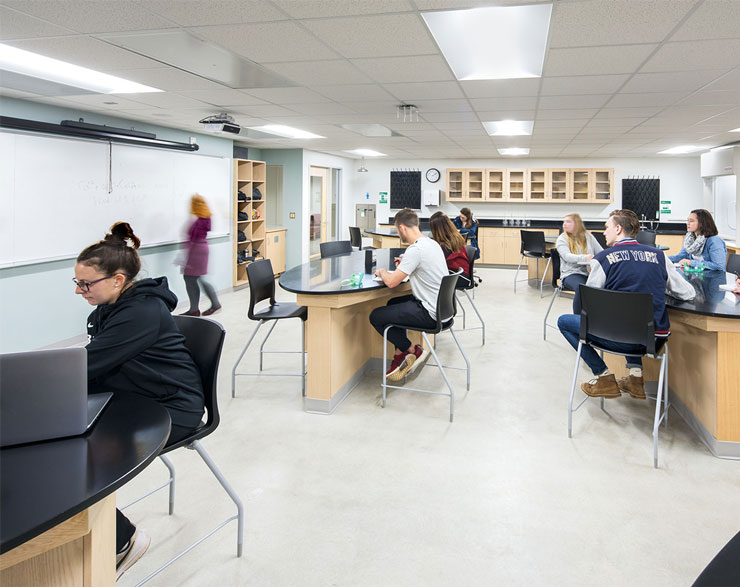 Students look toward the front of the lab at their teacher