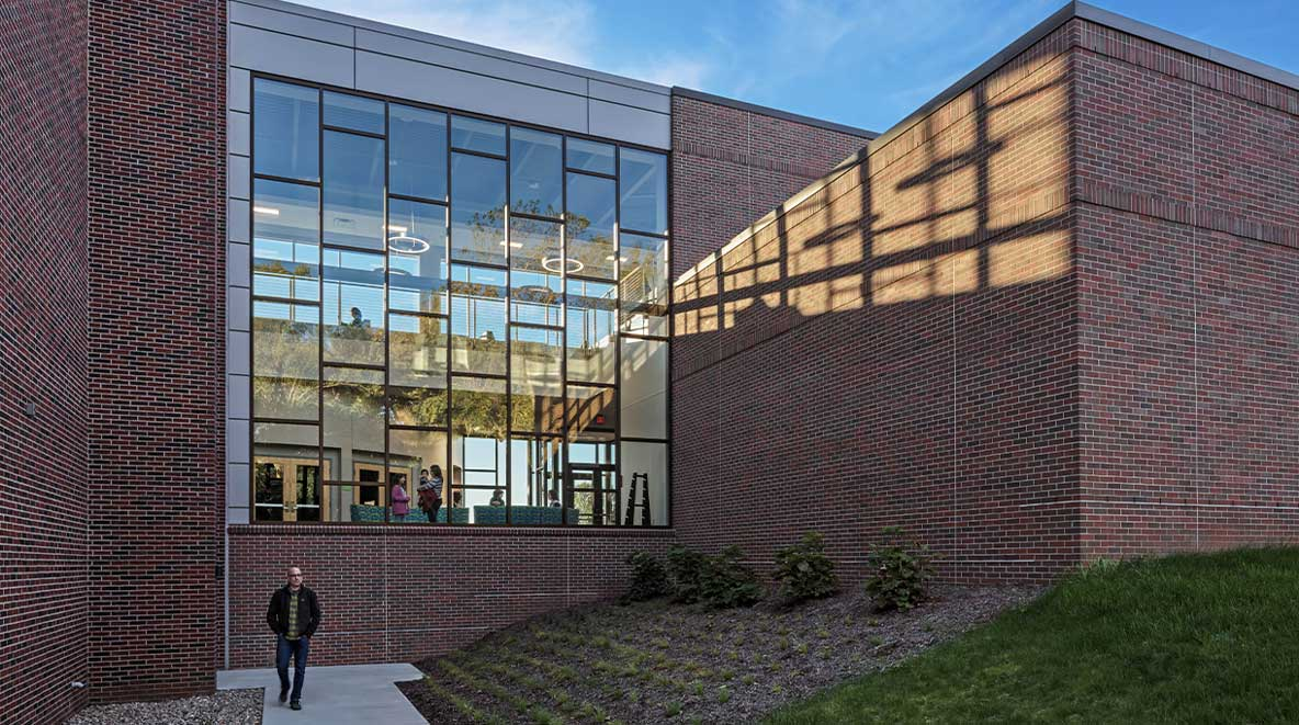 A glass wall of windows shows a sneak peak of what is inside the Grace College science complex