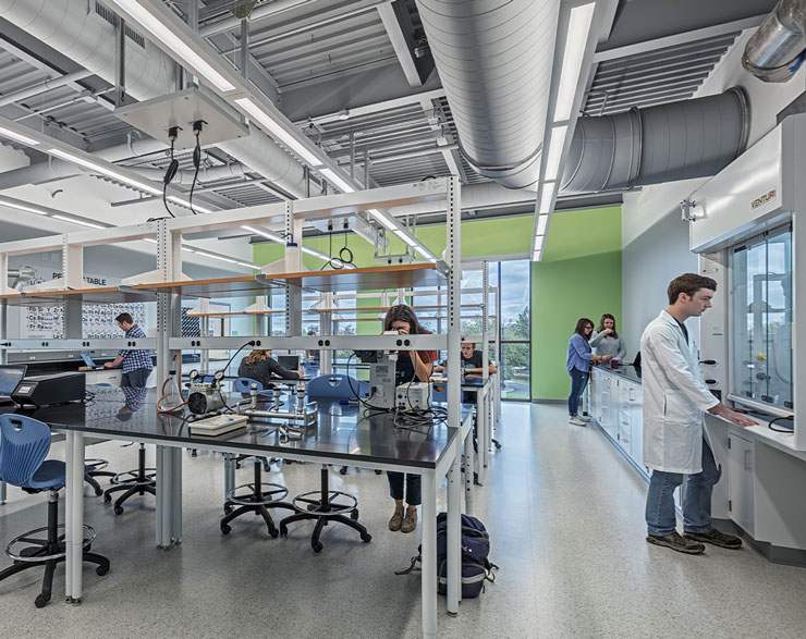 Students gather at a central table in the middle of a lab
