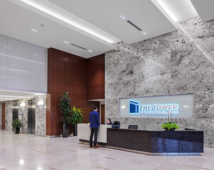 A receptionist desk is backed by a floor-to-ceiling granite wall