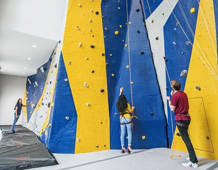 Two students stand at the bottom of the rock-climbing wall