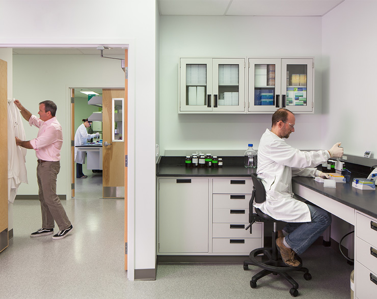 One man enters the lab, another is sitting down and using test tubes