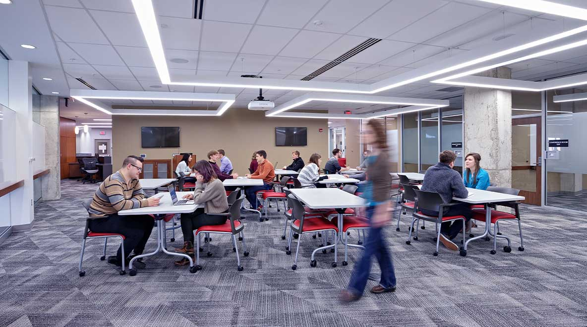 Many students are seen working in an open collaboration area