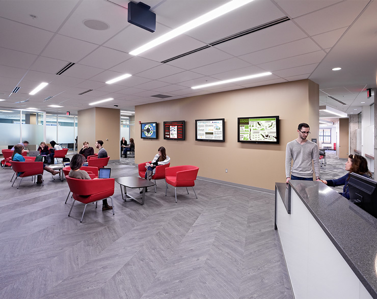 Students sit with others in a large open space next to the reception desk
