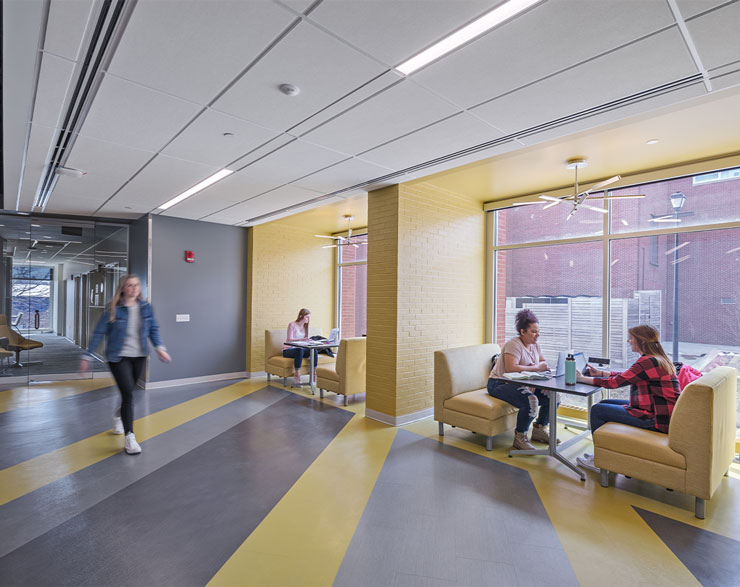 Large yellow booths line the wall of a corridor, providing space for students to gather