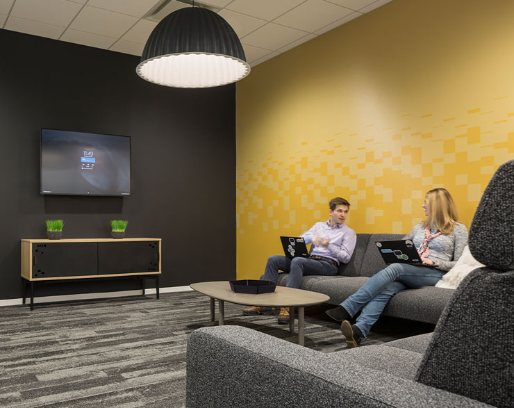 Employees talk in a huddle room