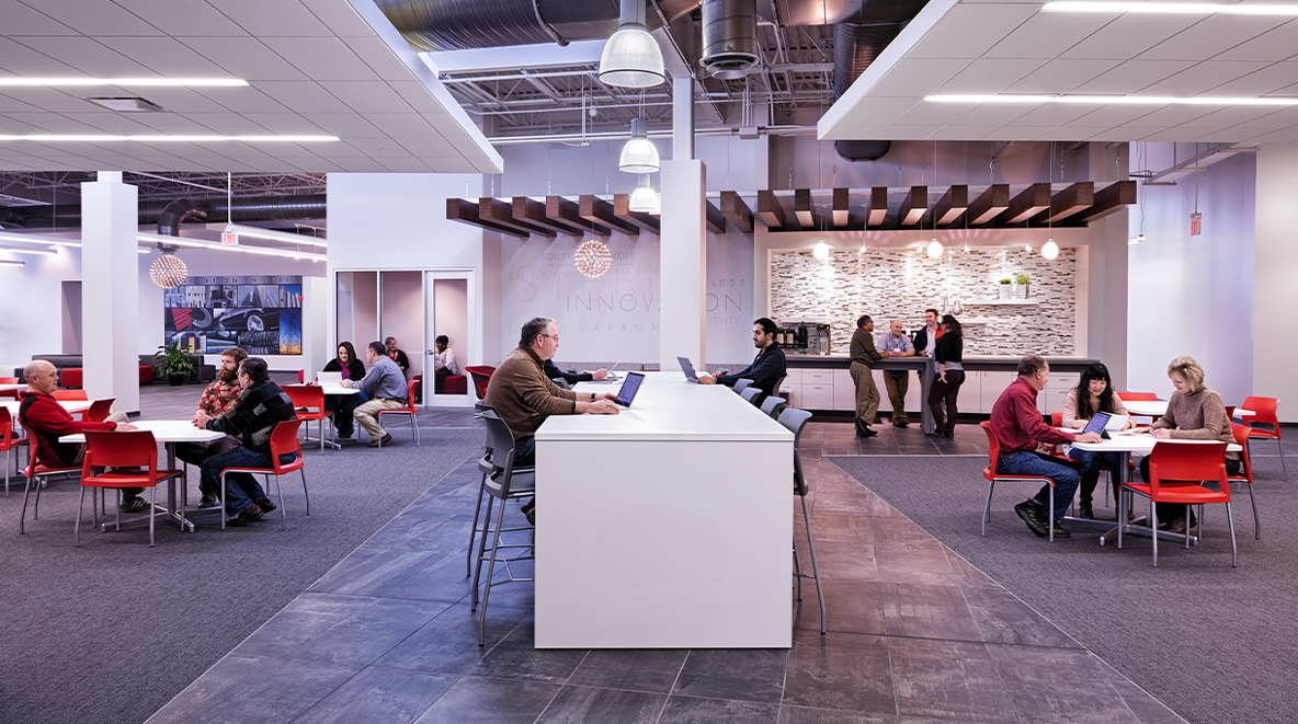 Employees work in an open collaboration space with tables and chairs