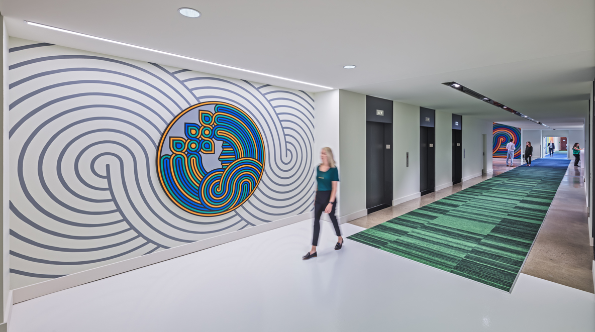 A P&G employee walks past a green and blue piece of art on the wall