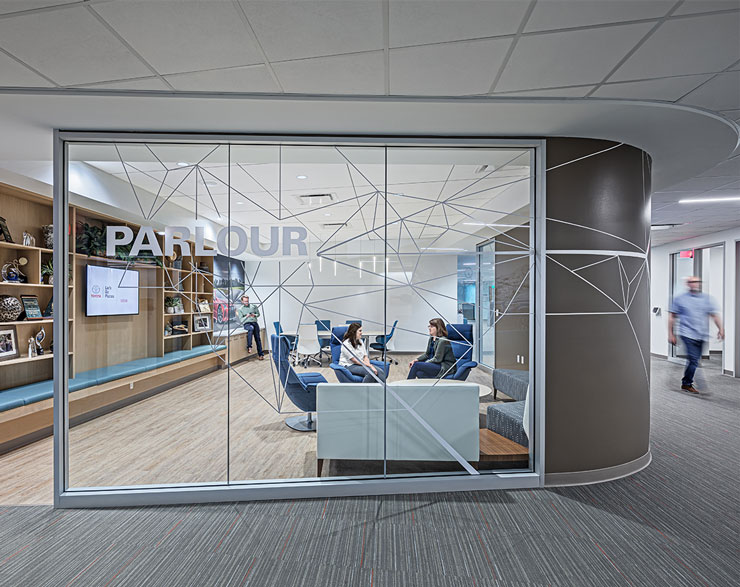 Employees collaborate behind a clear glass wall with privacy vinyl