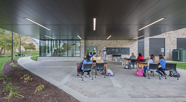 Students are seen in the outdoor classroom by the lake